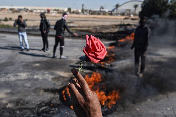 Un trandafir ridicat deasupra cauciucurilor care ard, în timpul protestelor antiguvernamentale din Irak. Foto: HAIDAR HAMDANI/AFP/Getty Images/Guliver