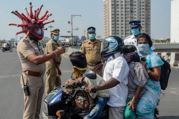 Polițist din India poartă o cască în formă de virus, în timp ce explică restricțiile impuse de autorități pentru a limita răspândirea coronavirusului. Foto: ARUN SANKAR/AFP/Getty Images/Guliver