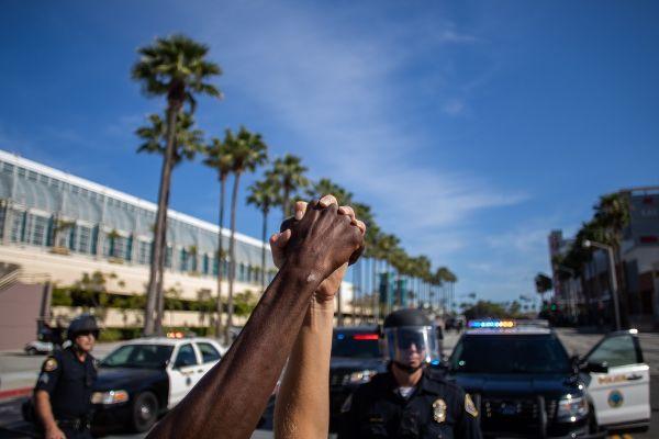 Un afro-american și un caucazian își stâng mâna în fața polițiștilor, în timpul unui protest față de moartea lui George Floyd. Tot mai multe proteste izbucnesc în SUA, după ce un american de culoare fost omorât de un polițist. Foto: AFP/Getty Images