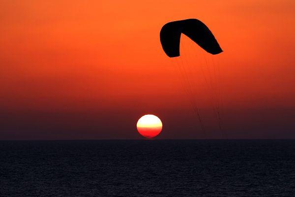 O persoană practică kite surfing, în timp ce soarele apune în Mediterana, în Netanya, Israel. Foto: JACK GUEZ/AFP/Getty Images/Guliver
